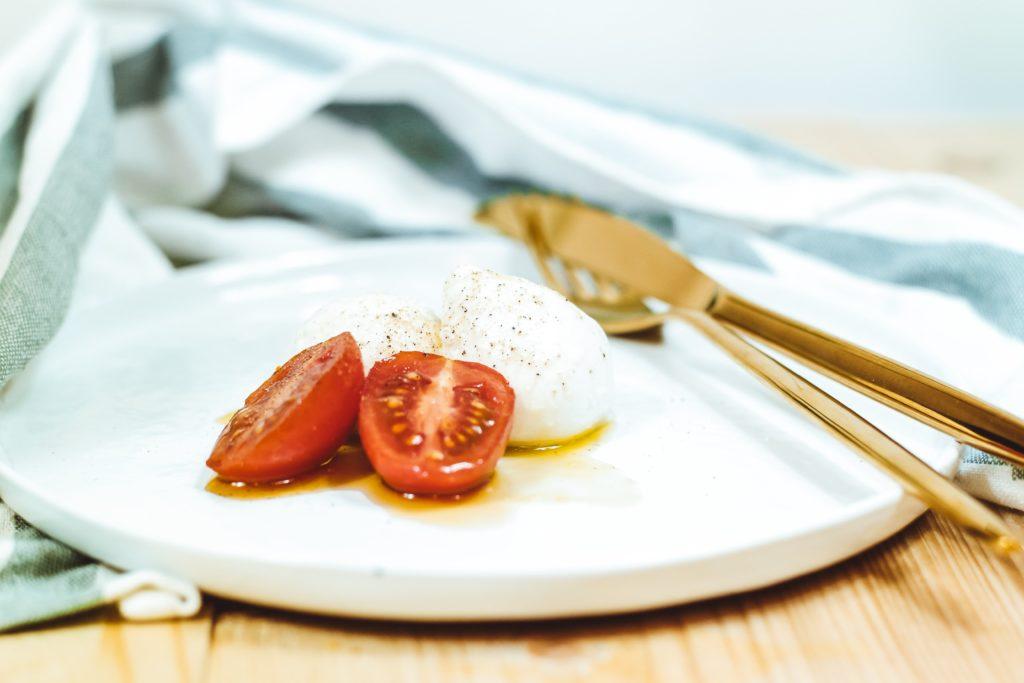 Photo d'une assiette contenant une boule du fromage italien mozzarella et une tomate.