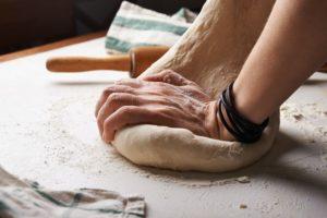Main en train de pétrir une pâte à pizza maison avec, dans le fond, un rouleau à pâtisserie.