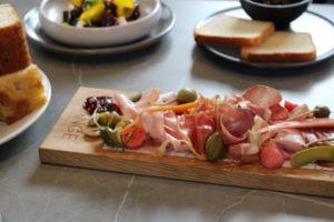Planche de charcuterie italienne haut de gamme avec du jambon cru italien, des câpres et des olives.