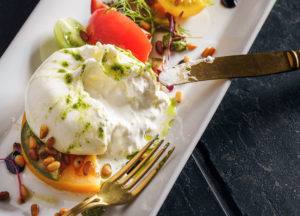 Belle assiette de burrata IGP fondante avec salade et melon