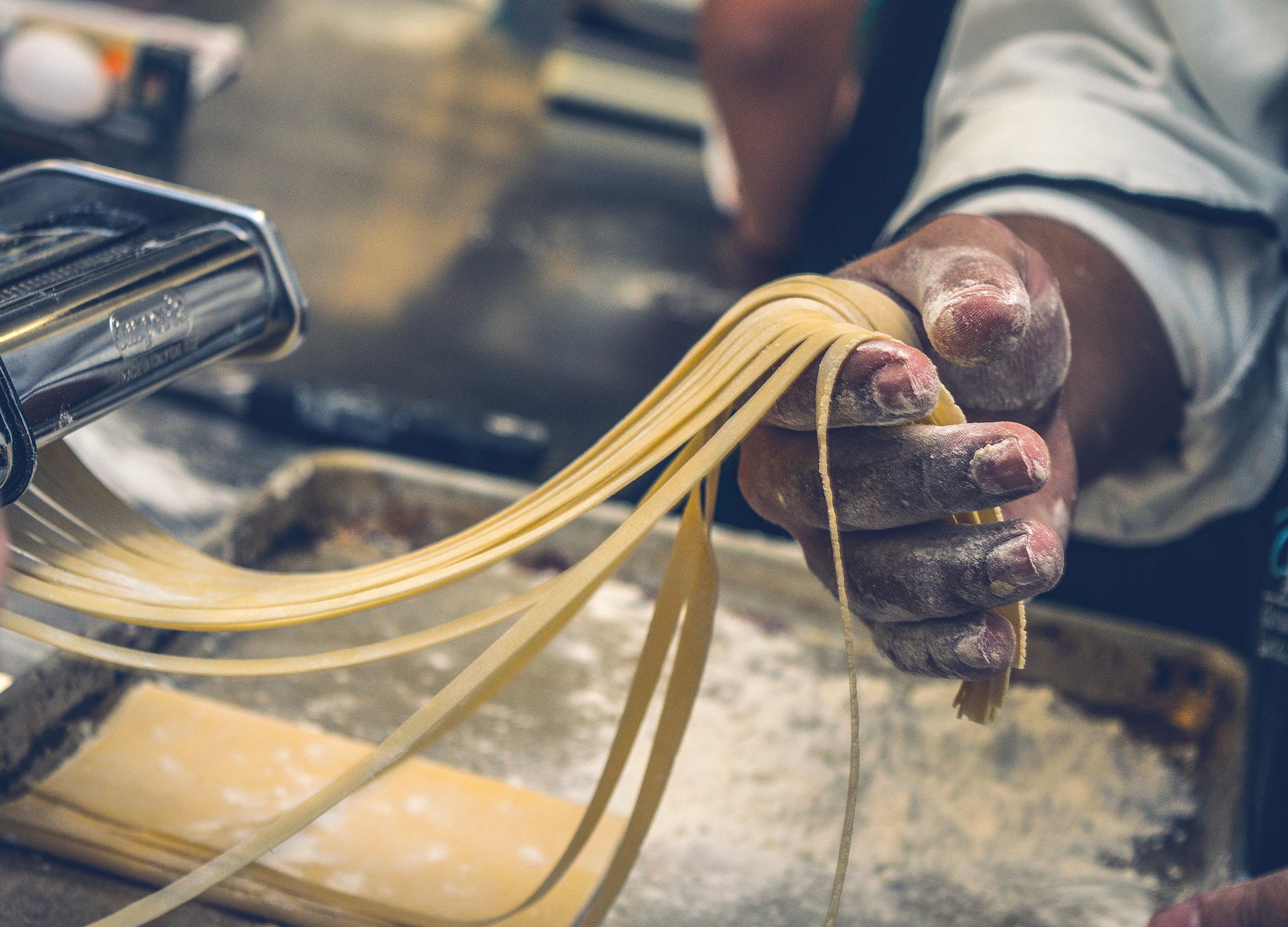 pâtes fraiches italiennes sortant d'un laminoir et retenues par une main