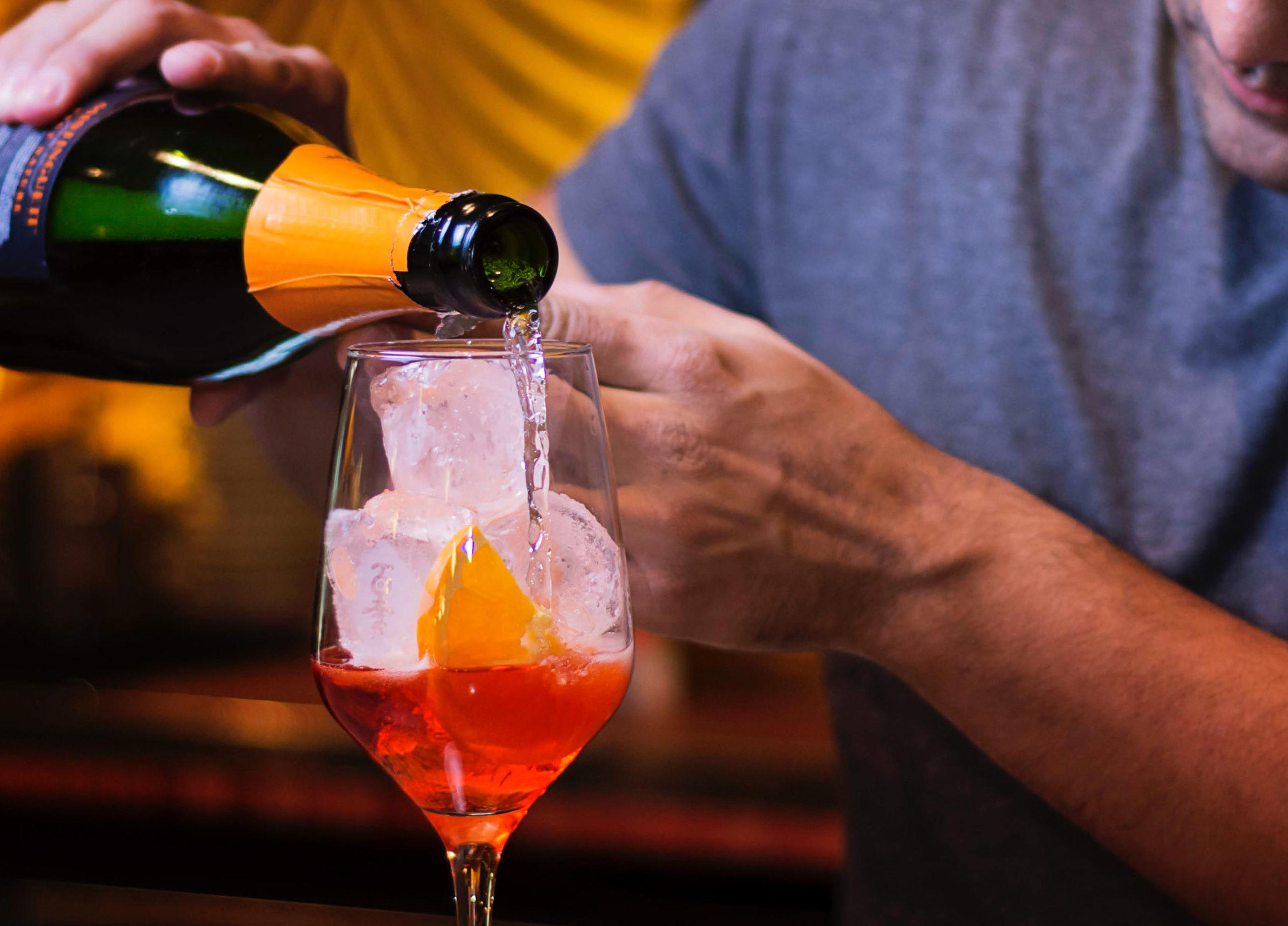 Photo d'un homme en train de verser du prosecco dans un verre contenant de l'Apérol afin de faire un Spritz